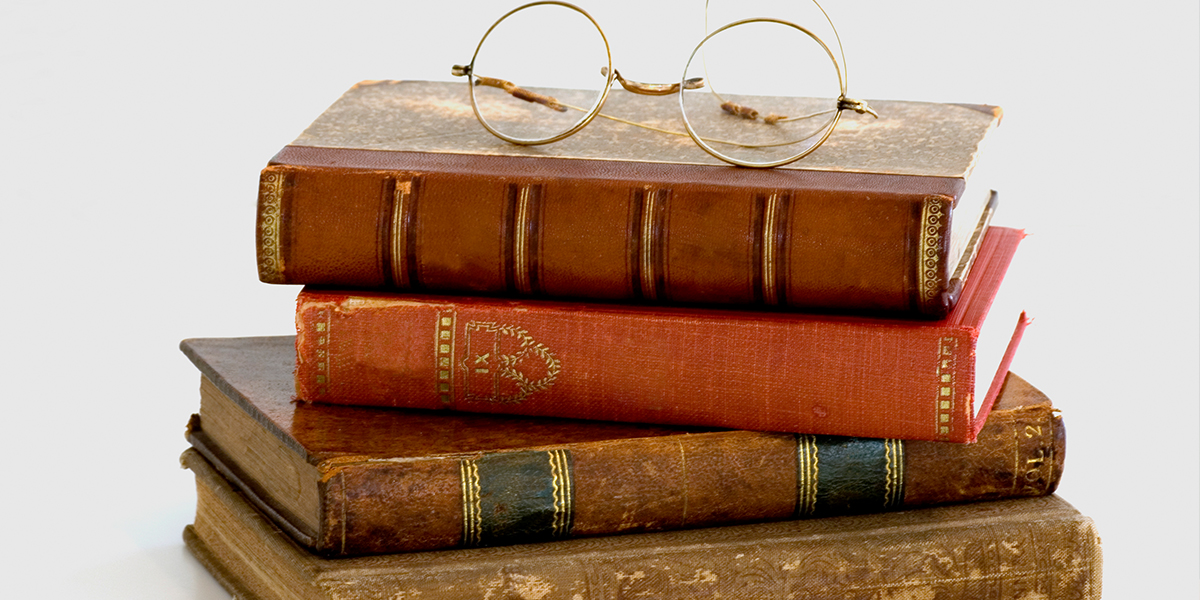 a stack of books with glasses on top of the stack