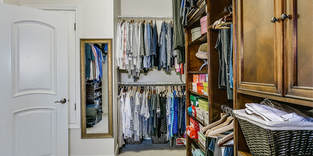 a master closet with clothes hanging in the closet